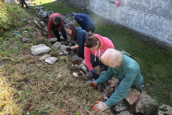 Članice Odbora za varstvo kulturne dediščine ob popravljanju podpornega zidu okoli cerkvice sv. Helene na Gradišču pod vodstvom Borisa Čoka (foto: Darja Kranjc)