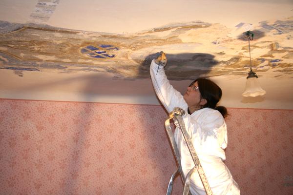Restavratorka pri strganju beleža iz dekorativnih poslikav